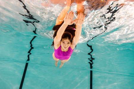 Photo for Attractive woman diving underwater in pink swimsuit in swimming pool - Royalty Free Image