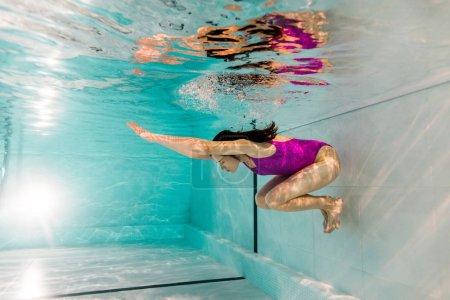 Photo pour Femme nageant sous l'eau en maillot de bain en eau bleue - image libre de droit