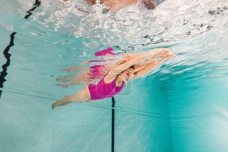 Photo pour Femme nageant dans googles sous l'eau dans la piscine - image libre de droit