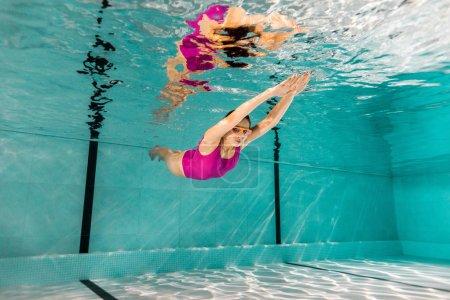 Photo pour Femme nageant dans les googles et maillots de bain rose sous l'eau - image libre de droit