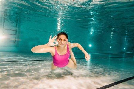 Photo pour Femme dans googles montrant ok signe tout en plongeant sous l'eau - image libre de droit