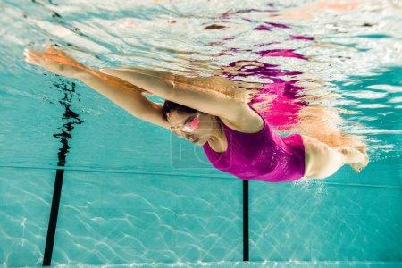 Photo pour Focalisé femme plongée dans googles dans piscine - image libre de droit