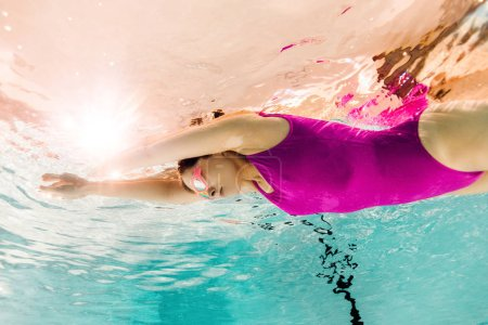 Photo for Focused woman swimming in googles underwater in swimming pool - Royalty Free Image