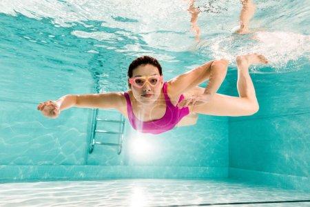 Foto de Sonriente mujer en traje de baño rosa y gafas de buceo bajo el agua en la piscina - Imagen libre de derechos