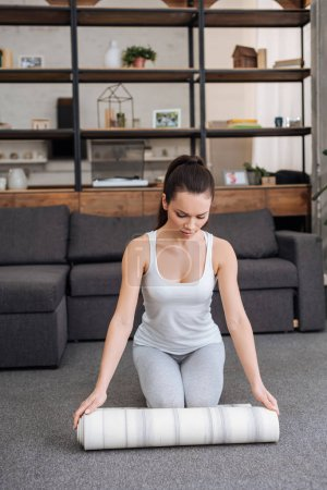 young woman rolling fitness mat for practicing yoga at home