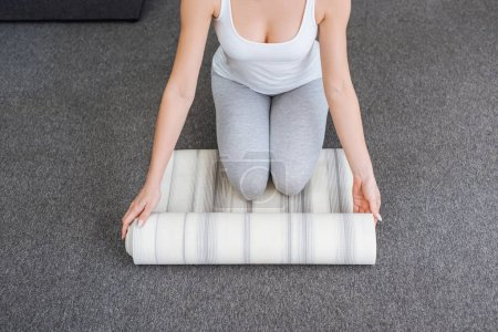 cropped view of woman rolling fitness mat for practicing yoga at home
