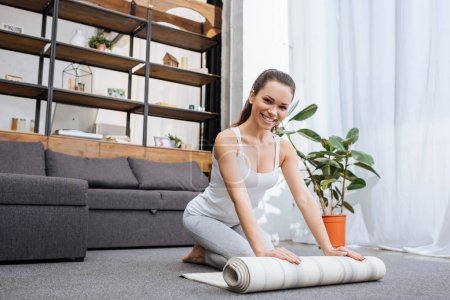 selective focus of smiling woman rolling fitness mat for practicing yoga at home