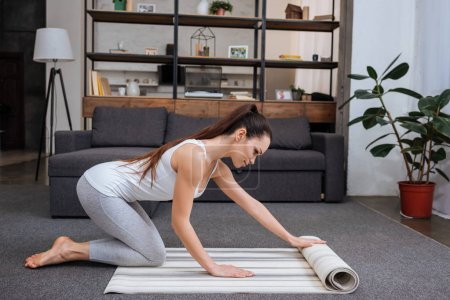 beautiful young woman rolling fitness mat for practicing yoga at home