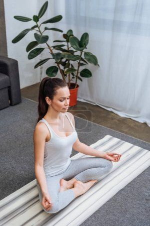 selective focus of beautiful young woman sitting in lotus pose and meditating at home