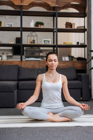 beautiful young woman sitting in lotus pose and meditating at home in living room