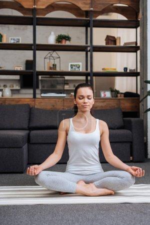Photo pour Belle jeune femme assis en posture de lotus et de méditer à la maison dans le salon - image libre de droit