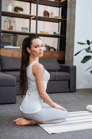 Photo for Beautiful woman sitting on fitness mat and practicing hero pose at home - Royalty Free Image