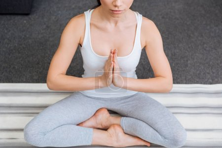cropped view of woman meditating in lotus pose at home