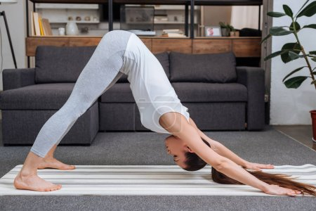 young woman practicing downward facing dog pose at home