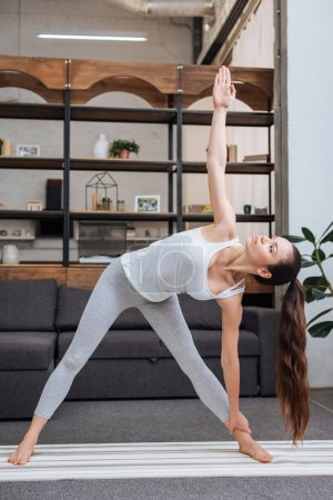 young woman practicing extended triangle pose at home in living room