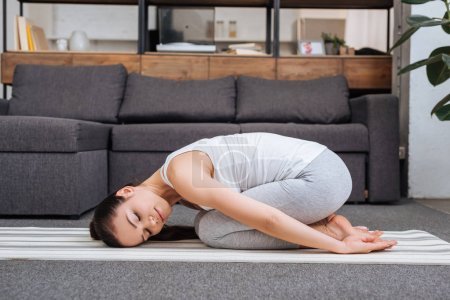 Photo for Woman doing relaxation exercise at home in living room - Royalty Free Image