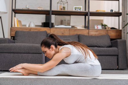 woman practicing seated forward fold pose on fitness mat at home in living room