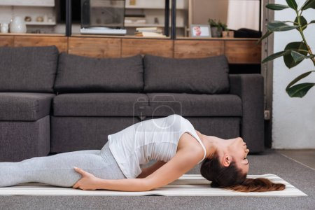 Photo for Woman practicing fish pose at home in living room - Royalty Free Image