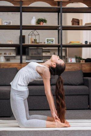 mujer practicante camello pose en casa en sala de estar