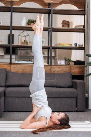 mujer practicante soportado hombrostand en casa en sala de estar