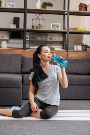 Photo for Sportswoman sitting on fitness mat and drinking water from sport bottle in living room - Royalty Free Image