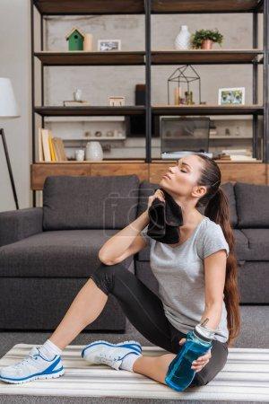 Photo pour Fatigué de sportive essuyant le visage avec une serviette après le travail dans la salle de séjour - image libre de droit