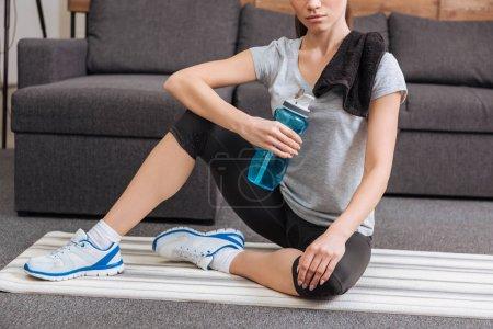 Foto de Vista recortada de deportista con botella toalla y deporte sentado en la sala de estar - Imagen libre de derechos