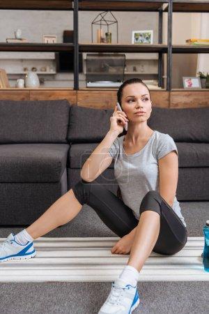Photo pour Séduisante sportive assis sur des tapis de fitness et de parler au smartphone à la maison - image libre de droit
