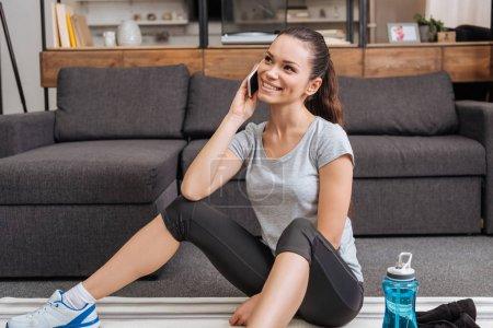 Photo pour Séduisante sportive souriante, assis sur des tapis de fitness et de parler au smartphone à la maison - image libre de droit