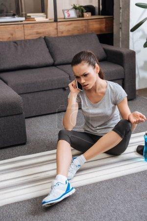 deportista frustrado sentado en la alfombra de fitness y hablando en el teléfono inteligente en casa