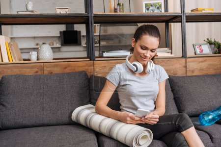 Photo for Attractive sportswoman with headphones sitting on couch and using smartphone at home - Royalty Free Image