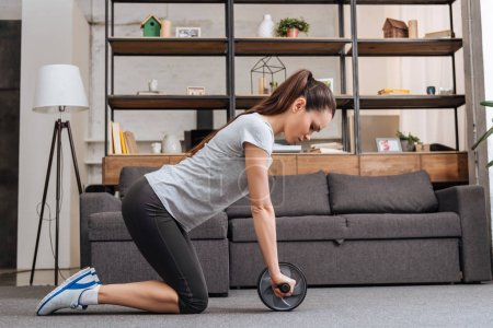 Photo for Focused sportswoman training with ab wheel at home - Royalty Free Image
