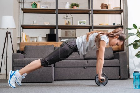 Photo for Focused sportswoman exercising with ab wheel at home - Royalty Free Image