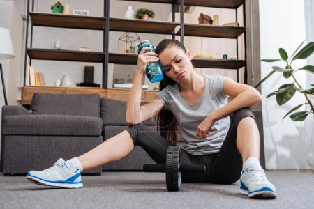 tired sportswoman with sport bottle after training with ab wheel at home