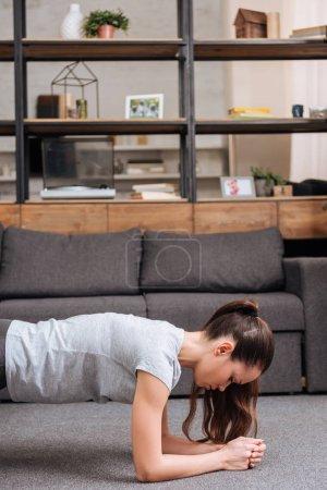 Foto de Deportista enfocada haciendo ejercicio de tablón en casa en salón - Imagen libre de derechos