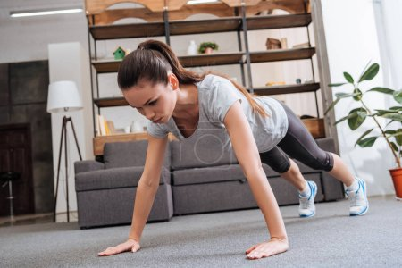 beautiful concentrated sportswoman doing plank exercise at home
