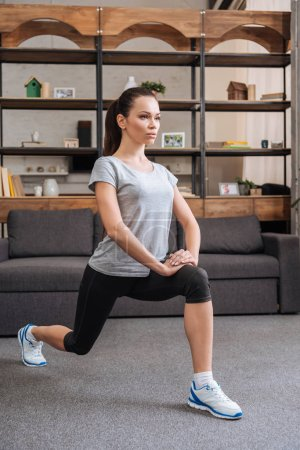 concentrated sportswoman doing lunge exercise at home