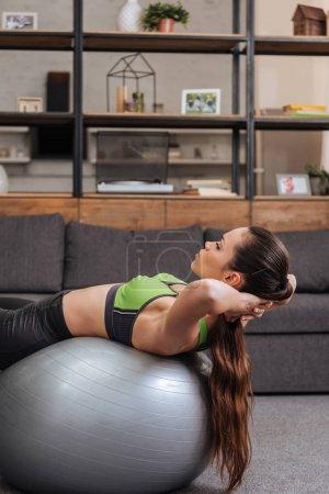 Photo pour Mise au point sélective de sportive ciblée exercice avec ballon de fitness à la maison - image libre de droit