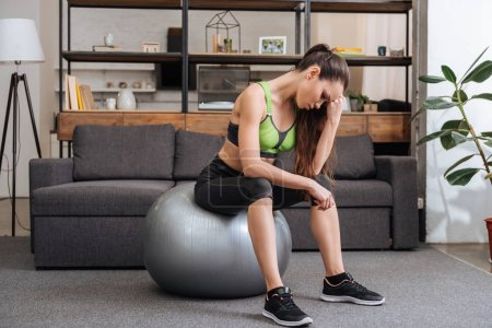 tired sportswoman sitting on fitness ball at home in living room