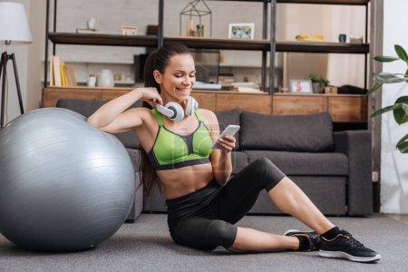 Foto de Sonriente la deportista en auriculares sentado con la bola de la aptitud y uso de smartphone en casa - Imagen libre de derechos