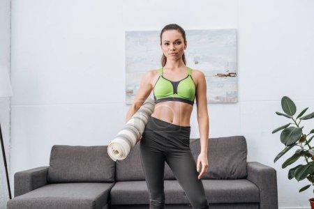 Photo pour Belle sportive athlétique avec tapis de fitness regardant la caméra à la maison - image libre de droit