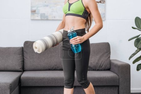 Photo for Cropped view of athletic sportswoman with fitness mat and sport bottle at home - Royalty Free Image