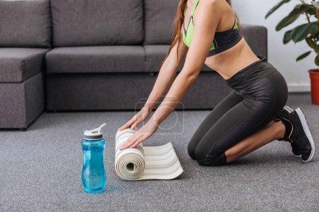 partial view of athletic sportswoman with fitness mat and sport bottle at home