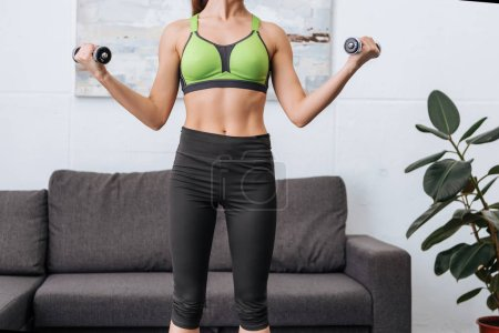 Photo for Partial view of sportswoman exercising with dumbbells at home - Royalty Free Image