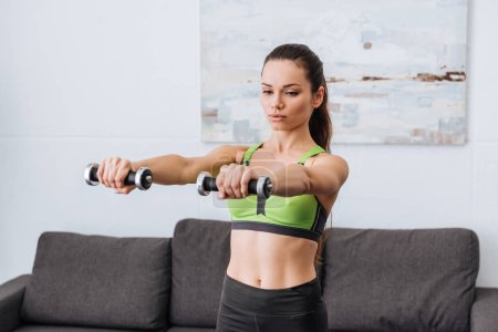 selective focus of beautiful sportswoman working out with dumbbells at home