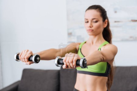 Photo for Sportswoman working out with dumbbells at home with copy space - Royalty Free Image