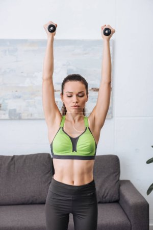 Photo for Beautiful sportswoman exercising with dumbbells at home - Royalty Free Image