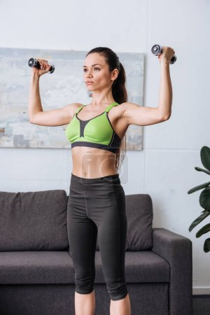 Photo for Beautiful concentrated sportswoman training with dumbbells at home - Royalty Free Image