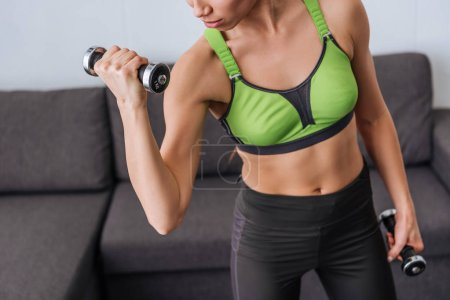 Photo for Partial view of athletic sportswoman exercising with dumbbells at home - Royalty Free Image