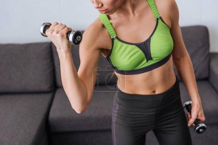 Photo pour Vue partielle de sportive athlétique exercice avec des haltères à la maison - image libre de droit
